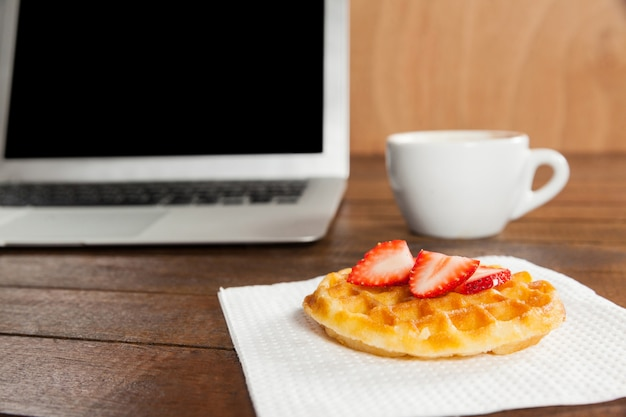 Office desk with strawberry waffle, laptop and coffee cup
