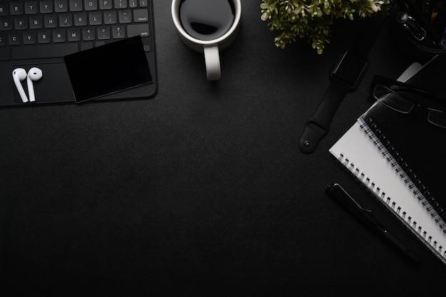 Office desk with wireless earphone, smart watch, notebook and keyboard.