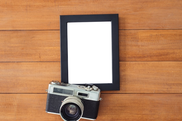 古いカメラとポスターモックアップテンプレートとオフィスデスク木製のテーブル。コピースペースを持つトップビュー