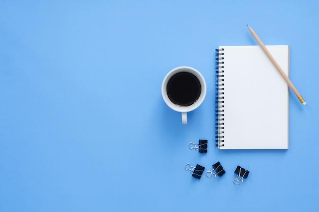 Офисное рабочее место - плоский макет сверху с изображением рабочего пространства с белой пустой записной книжкой