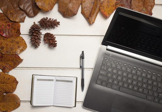 白いテーブルの背景にペンでラップトップとノートブックとオフィスデスクワークスペース。フラットレイ