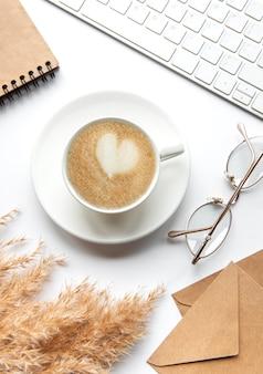 Рабочее место офисного стола с тетрадью, кофе и пампасной травой. плоская планировка, вид сверху, бизнес, концепция работы.