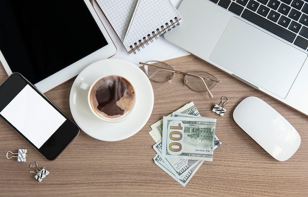 Office desktop. laptop with office supplies and money on the table. Premium Photo