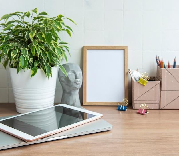 テーブルの上に事務用品を備えたオフィスデスクトップラップトップ