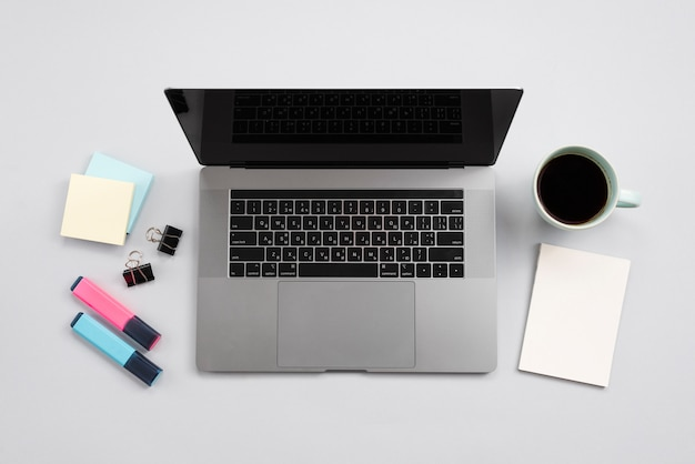 Office desktop with laptop and a coffee cup