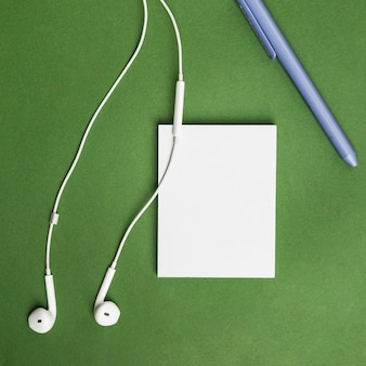Office desktop with a paper sheet and earphones
