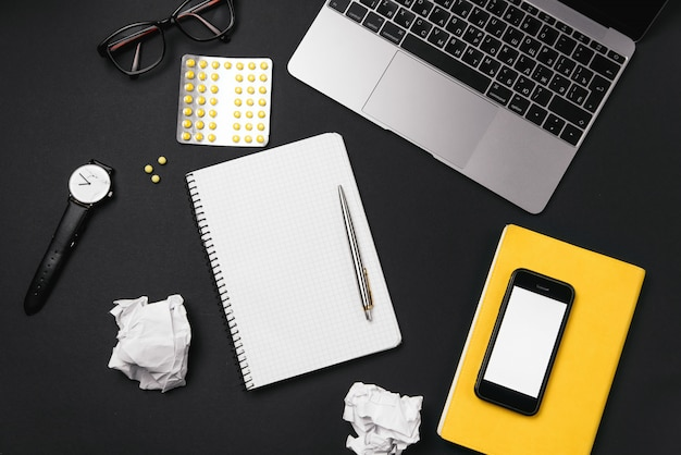 Office desktop with soothing pills and crumpled paper balls, white sheet of paper with free copy space, laptop and office supplies.