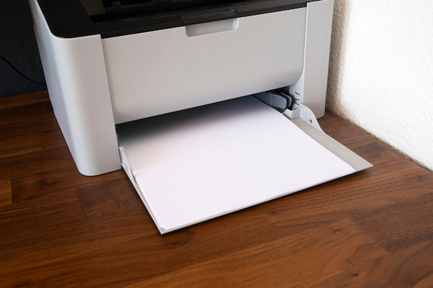 Office digital printer, copier and paper on wooden desk, fax machine close-up