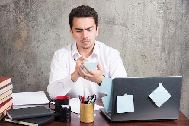 Офисный служащий сердито смотрит на свой телефон на офисном столе.