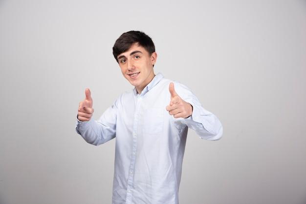 Impiegato d'ufficio in abbigliamento formale che mostra i pollici in su sul muro grigio.