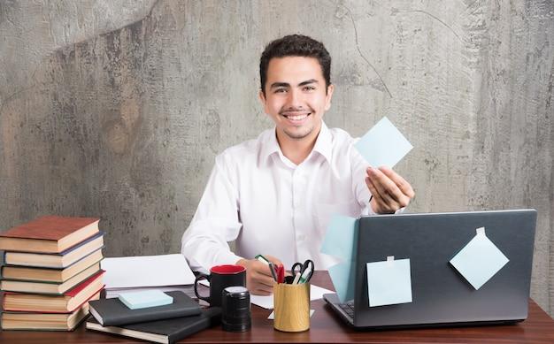 オフィスの従業員は、オフィスのデスクでメモ帳を喜んで見せています。