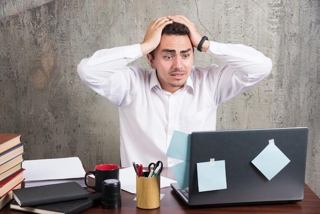 Офисный служащий, держащий голову с большой работой за офисным столом.