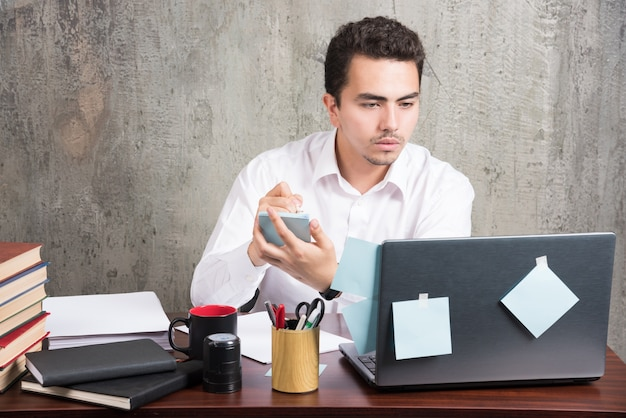 Офисный служащий, глядя на ноутбук и держа телефон за офисным столом.