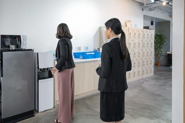 점심 시간에 물을 마시기 위해 대기열에 서있는 사무실 직원
