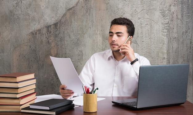 Impiegato di ufficio parlando al cellulare e tenendo fogli di carta. foto di alta qualità