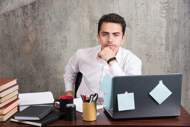 Impiegato di ufficio che pensa al lavoro alla scrivania.