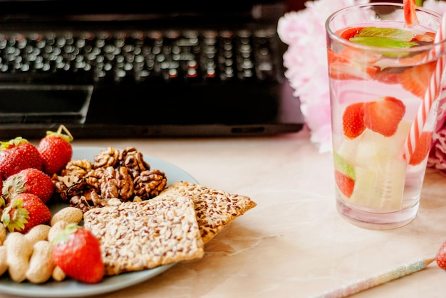 Office employee with laptop, healthy snack, water with strawberry and cucumber