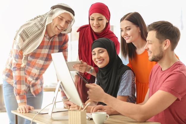 オフィス従業員とそのイスラム教徒の同僚がオフィスでビジネスミーティングを行う
