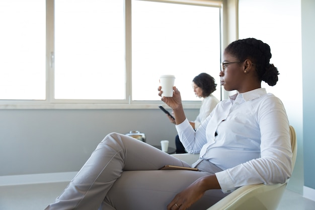 Office employees drinking coffee in office lounge