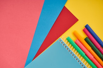 Office equipments with colorful papers on yellow background