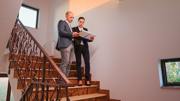 Office executive holding clipboard discussing with company manager on staircase of business building analysing reports. group of professional businesspeople working in modern financial workplace.