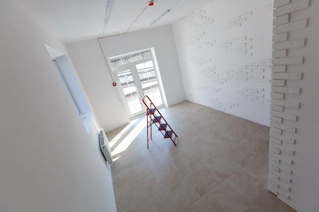 벽돌을 벽, 건축, 개량으로 사용하는 사무실 확장. 창문과 벽돌 벽의 개조, 확장, 정밀 검사 및 재건축이 있는 작은 방의 내부.
