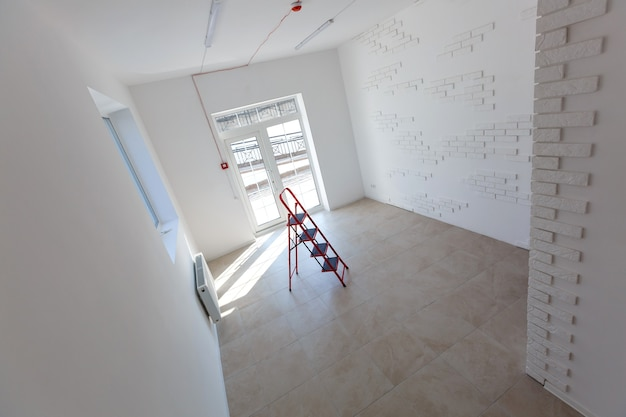 Office extension that uses bricks as a wall, construction, improvement. interior of small room with window and bricks walls renovation, extension, overhaul and reconstruction.