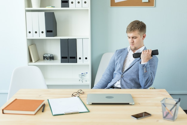 Office, fitness and people concept - business man working and doing sport at her office