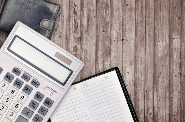 電卓、アドレス帳、黒い財布のオフィスフラットレイアウト構成