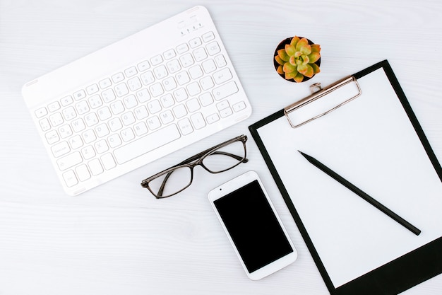 白いキーボード、老眼鏡、ペット、ノートブックのあるオフィスフラットレイ