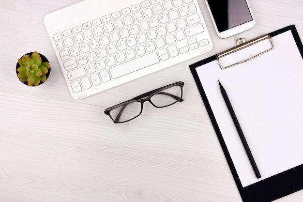 Office flatlay with white keyboard, reading glasses, pet and notebook