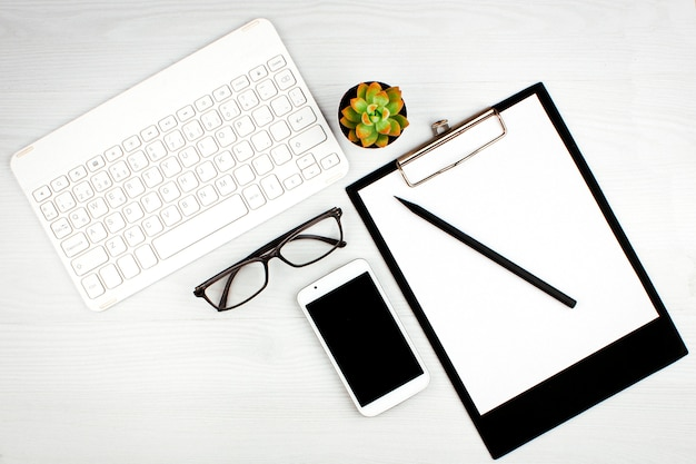 Office flatlay with white keyboard, reading glasses, pet and notebook.