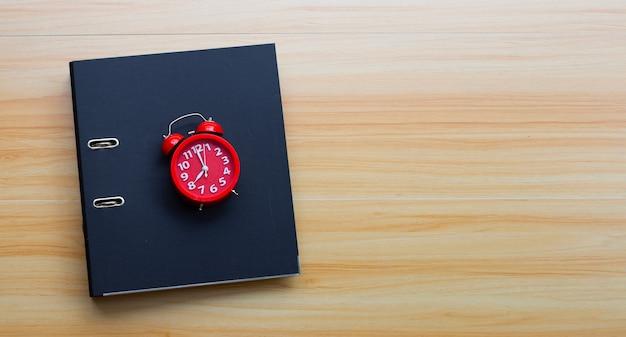 木製のテクスチャの背景に赤い目覚まし時計とオフィスフォルダー。上面図