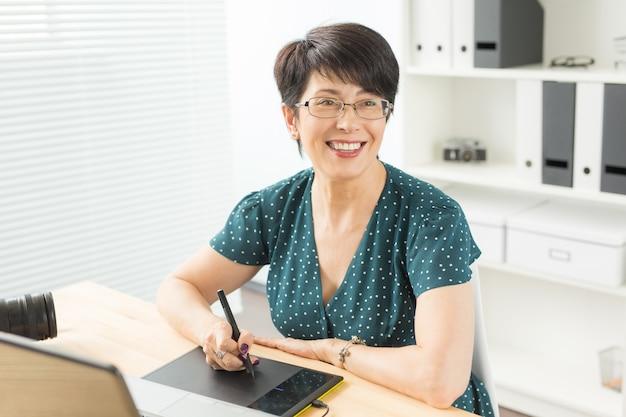 Офис, концепция графического дизайнера - деловая женщина, держащая цифровой планшет, рисуя эскиз