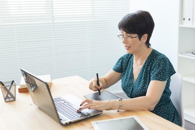Офис, графический дизайнер, цифровой - женщина среднего возраста, работающая в офисе с ноутбуком и цифровым