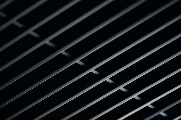 オフィスグリルの天井。モダンなブラックメタルグリル天井、吊り下げ式カバー。抽象的なデザインのテクスチャ。