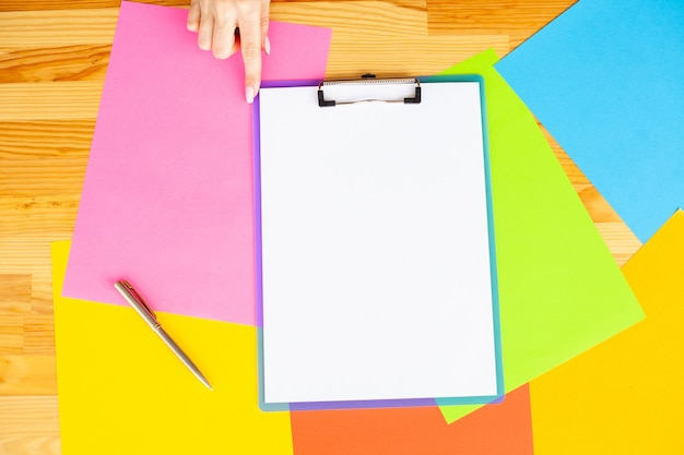 Office hand holding a folder with a blue color paper and pen