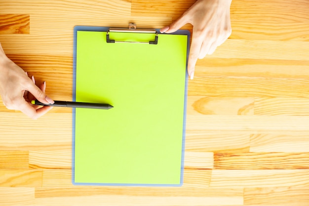 Office hand holding a folder with a green color paper on the background of the wooden table.