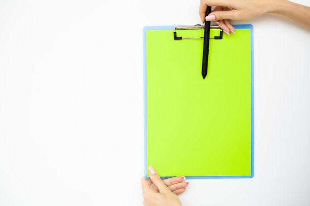 Office hand holding a folder with a green color paper and pen on the background of the white table. copyspace.