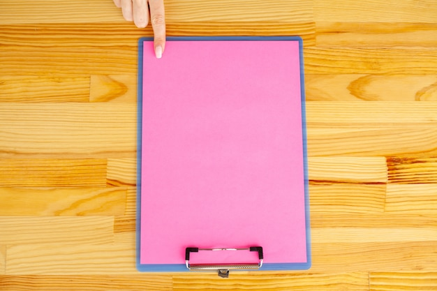 Office hand holding a folder with a pink color paper