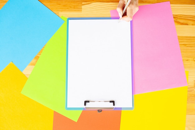 Office hand holding a folder with a white color paper and pen