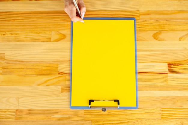 Office hand holding a folder with a yellow color paper and pen