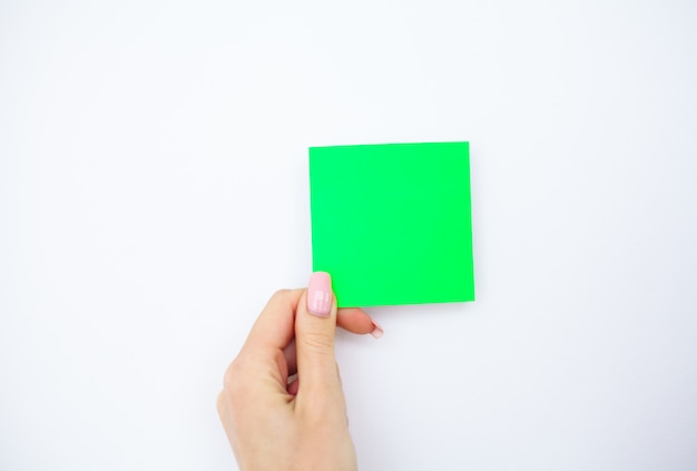 Office hand holding a green color sticker on white background