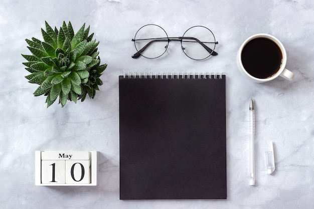 Office or home table, calendar may 10 notepad, coffee, succulent, glasses concept stylish workplace