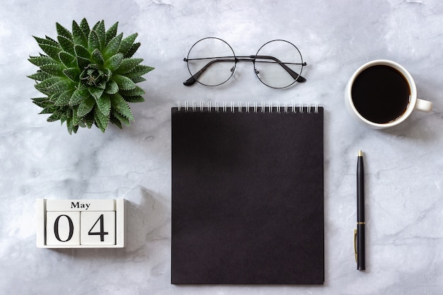 Office or home table, calendar may 4th. black notepad, cup of coffee, succulent, glasses