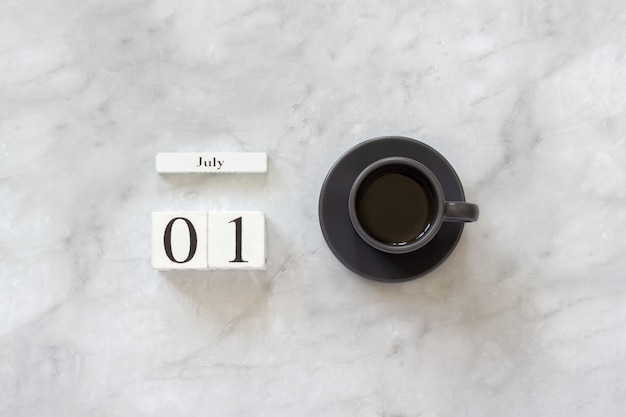 Office or home table desk. wooden cubes calendar july 1st and cup of coffee on marble background concept stylish workplace