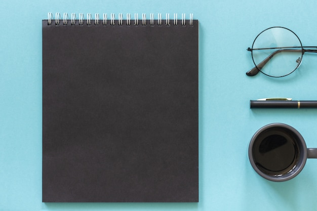 Office or home workplace. black color notepad, cup of coffee, spectacles, pen on blue