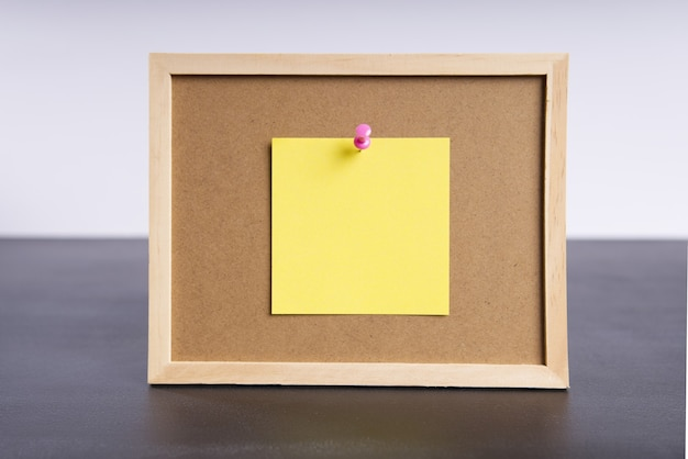 Office information board with attached yellow piece of paper with space for text