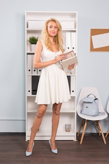 オフィス、インテリア、人々のコンセプト-金髪の若い女性がオフィスで写真家のポートフォリオを開きました