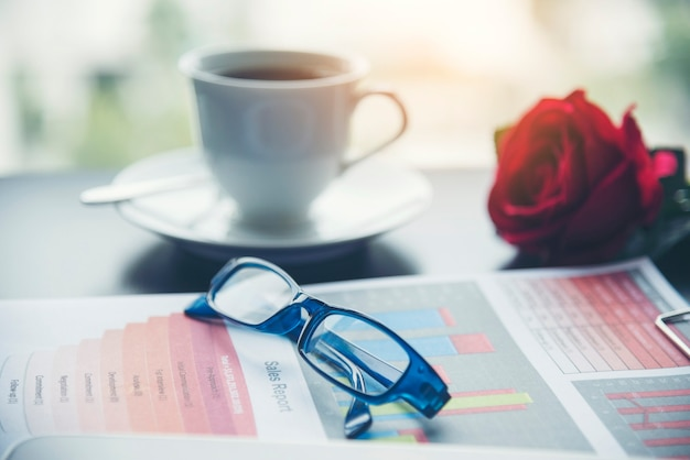 사무실 노트북 비즈니스 재무 문서 차트와 커피 컵이 있는 나무 테이블에 그래프. 사무실 책상에 평평한 노트북 컴퓨터 노트북. 비즈니스 작업 공간에 사람이 없는 비즈니스 그래프 차트 모형이 없습니다.